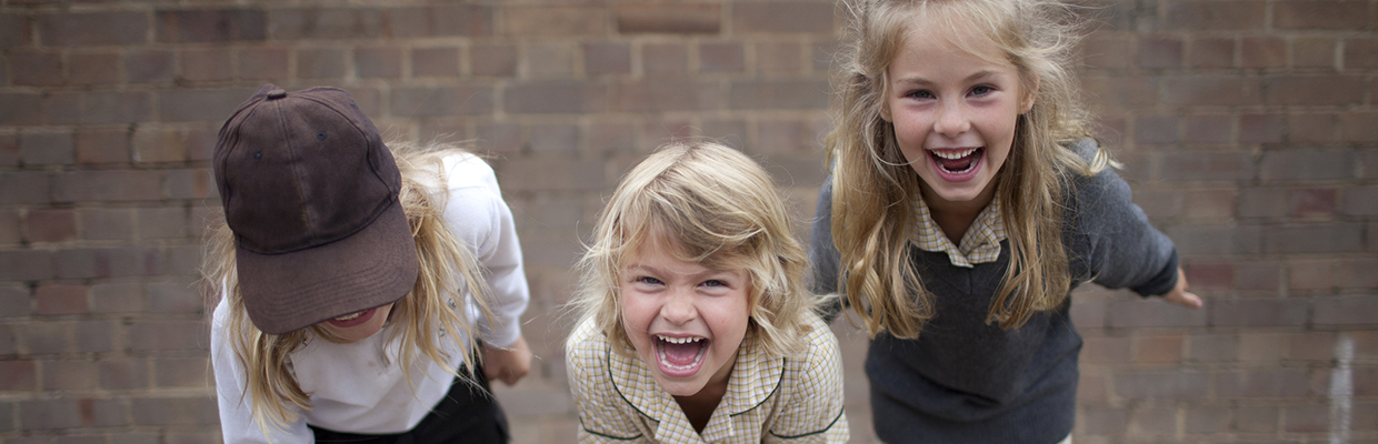 Three young school kids laughing in a school yard